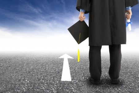 Image of a graduate standing on the road and forward arrow